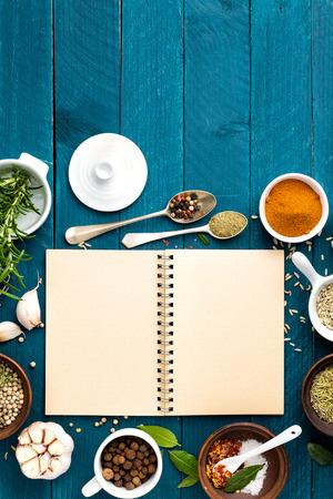culinaire achtergrond en receptenboek met diverse kruiden op houten tafel