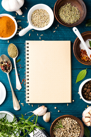 culinary background and recipe book with various spices on wooden table 스톡 콘텐츠