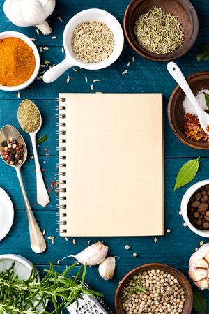 kulinarne: Kulinarny tło i książka kucharska z różnymi przyprawami na drewnianym stole