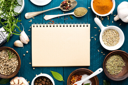 culinary background and recipe book with various spices on wooden table Foto de archivo