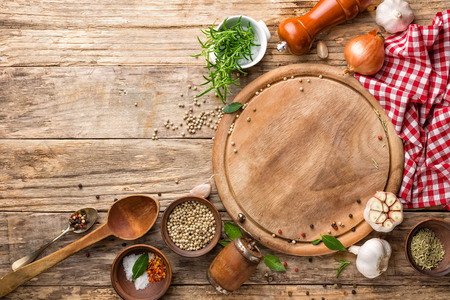 culinary background with empty cutting board and spices on wooden table Foto de archivo