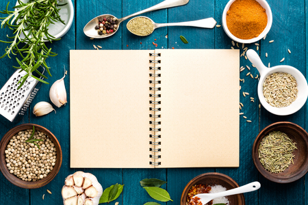 culinary background and recipe book with various spices on wooden table Stock Photo
