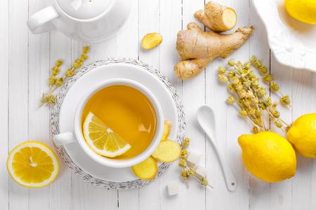 trompo de madera: té en una taza blanca con limón y jengibre Foto de archivo