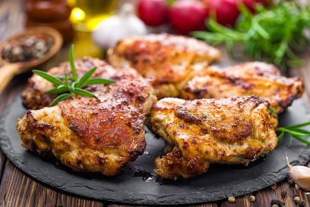 pollo a la brasa: muslos de pollo asado preparado en la mesa de madera Foto de archivo