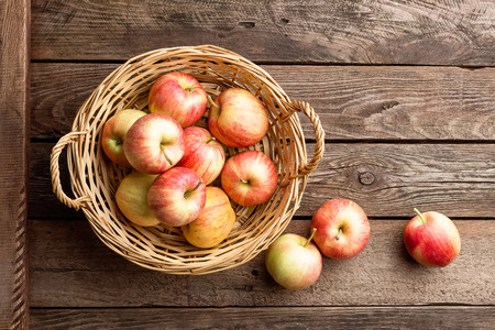 mimbre: Fresh red apples in wicker basket on wooden table.