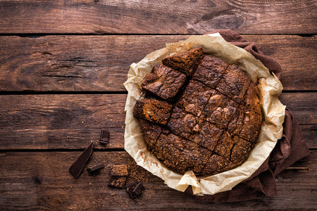 homemade: homemade chocolate brownie on dark wooden background, top view