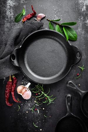 Gietijzeren pan en kruiden op black metal culinaire achtergrond, bekijken van bovenaf Stockfoto - 65191119