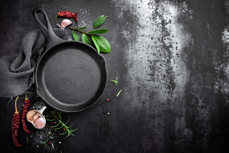 cast iron pan and spices on black metal culinary background, view from above Stock Photo