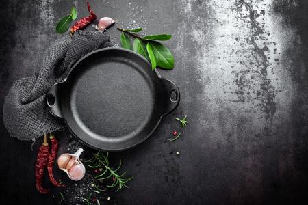 Gusseisenpfanne und Gewürze auf schwarzem Metall-kulinarischen Hintergrund, Ansicht von oben