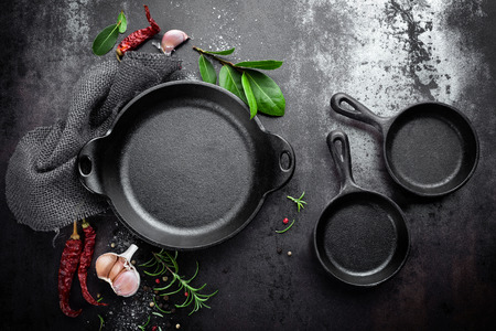 cast iron pan and spices on black metal culinary background, view from above Archivio Fotografico