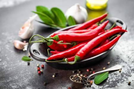 Rojos granos de pimienta de chile caliente y vainas en el fondo culinaria de metal oscuro de edad Foto de archivo - 65191157