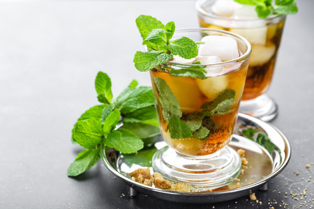 Mint Julep cocktail with bourbon, ice and mint in glass on black background Stock Photo