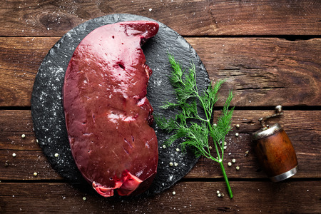 Raw liver on slate board on wooden background top view Stock Photo