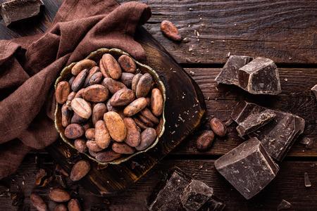 Cacao en grano y chocolate sobre fondo de madera