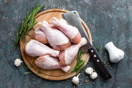 Cuisses de poulet non cuites crues, pilons sur planche de bois, viande avec ingrédients pour cuisiner, vue de dessus