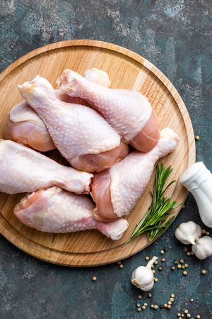 carne de pollo: Raw uncooked chicken legs, drumsticks on wooden board, meat with ingredients for cooking, top view Foto de archivo