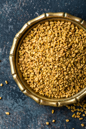 Fenugreek seeds on metal plate, spice, culinary ingredient Stock Photo