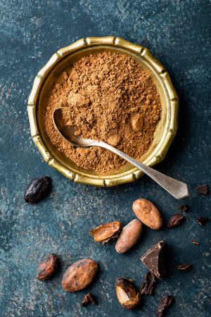 Cocoa powder, beans and dark chocolate pieces crushed, culinary background, top view Stock Photo