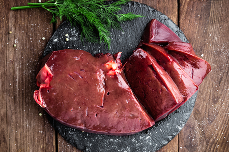 Raw liver on slate board on wooden background top view Stockfoto