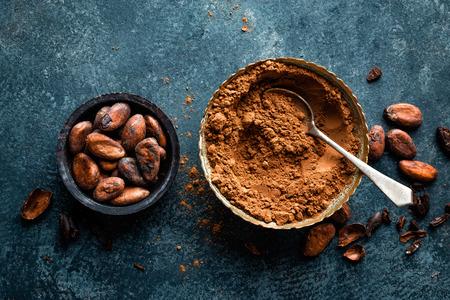 Cacaopoeder en cacaobonen op donkere achtergrond, hoogste mening Stockfoto