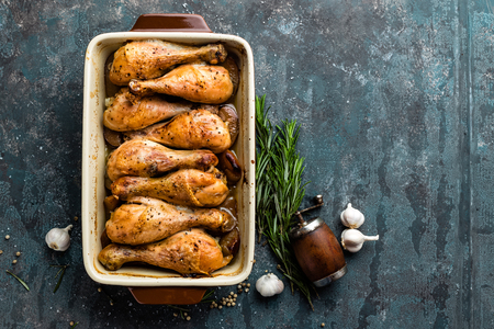 roast meat: Grilled fried roast chicken legs, drumsticks on dark background, meat with ingredients for cooking, top view