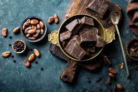 Dark chocolate pieces crushed and cocoa beans, top view Standard-Bild