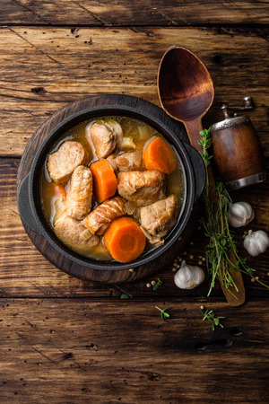 Meat stewed with carrots in sauce and spices in cast iron pot on dark wooden rustic background Stock Photo