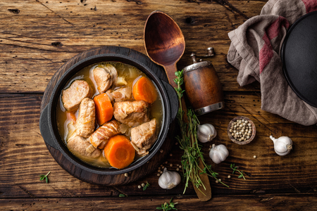 Meat stewed with carrots in sauce and spices in cast iron pot on dark wooden rustic background Stockfoto