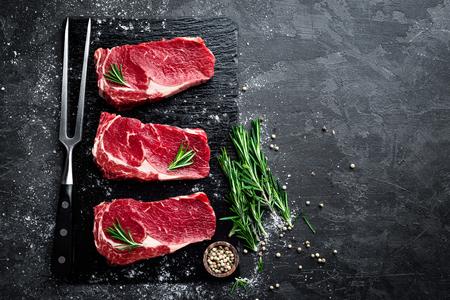 Raw meat, beef steak on black background, top view Foto de archivo