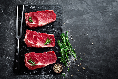 Raw meat, beef steak on black background, top view Imagens