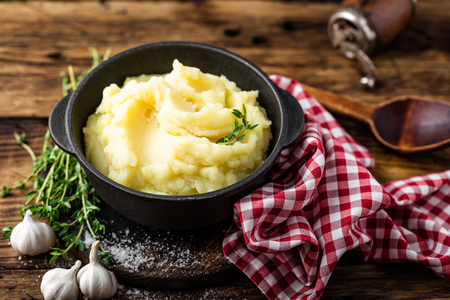 Mashed potatoes, boiled puree in cast iron pot on dark wooden rustic background Foto de archivo