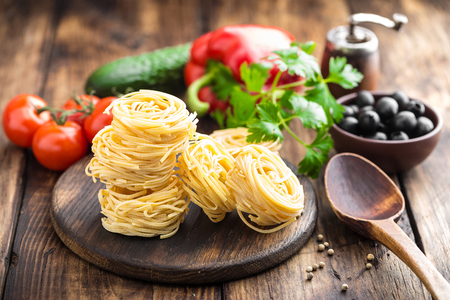 gourmet kitchen: Raw alluovo pasta, egg noodles with cooking ingredients on dark wooden rustic background, traditional italian cuisine