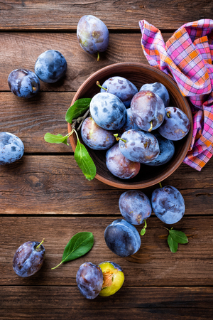 ciruela pasa: Fresh plums with green leaves on wooden rustic background, top view