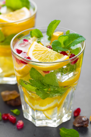 Lemon mojito cocktail with fresh mint and pomegranate, cold refreshing summer drink or beverage with ice