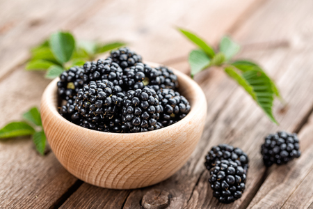 Fresh blackberry with leaves on wooden background close up