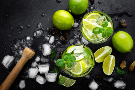 Refreshing mint cocktail mojito with rum and lime, cold drink or beverage with ice on black background, top view Stock Photo