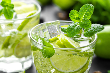 Summer mint lime refreshing cocktail mojito with rum and ice in glass on black background Stock Photo