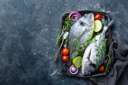 Fresh uncooked Dorado fish or sea bream with ingredients for cooking on dark background, top view Stock Photo