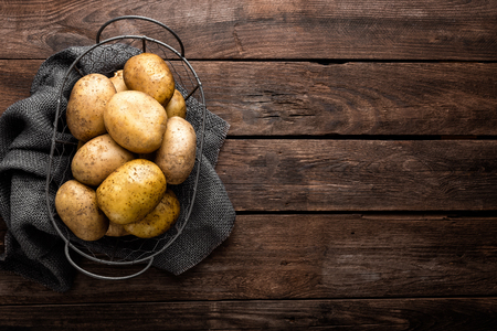 Raw potato on wooden background, top view Archivio Fotografico