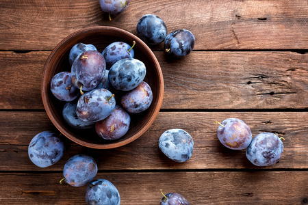 Fresh plums on wooden table, top view Stock Photo