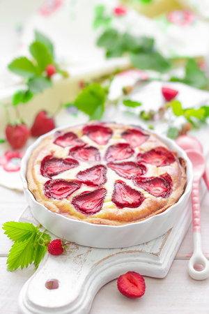 Delicious strawberry tart or cheesecake with fresh berries and cream cheese, closeup on white wooden rustic background Imagens