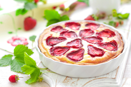 Delicious strawberry tart or cheesecake with fresh berries and cream cheese, closeup on white wooden rustic background Stock Photo