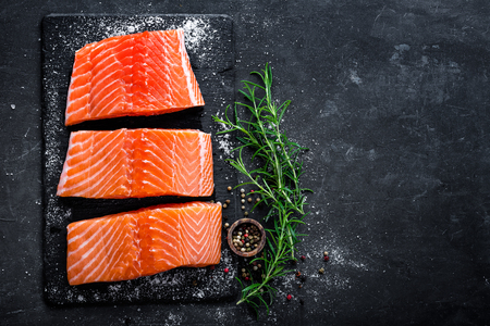 Raw salmon filet on dark slate background, wild atlanic fish