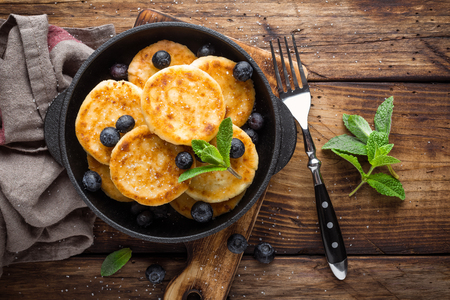 Delicious cottage cheese pancakes or syrniki with fresh blueberry in cast-iron pan on dark wooden rustic background, above view. Tasty breakfast.