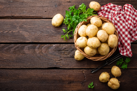 Raw potato in basket on wooden table, top view