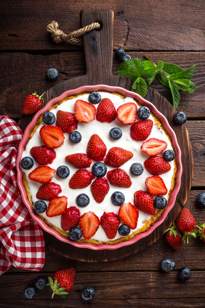 Delicious strawberry pie with fresh blueberry and whipped cream on wooden rustic table, cheesecake, top view Фото со стока