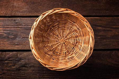 木製の背景、トップ ビューで空の籐のバスケット 写真素材