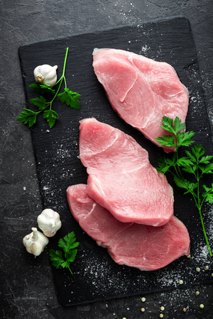 Raw meat, turkey steaks on black background, top view Stock Photo