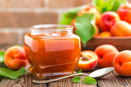 Apricot jam in a jar and fresh fruits with leaves Reklamní fotografie