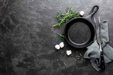 Empty cast iron frying pan on dark grey culinary background, view from above Stockfoto